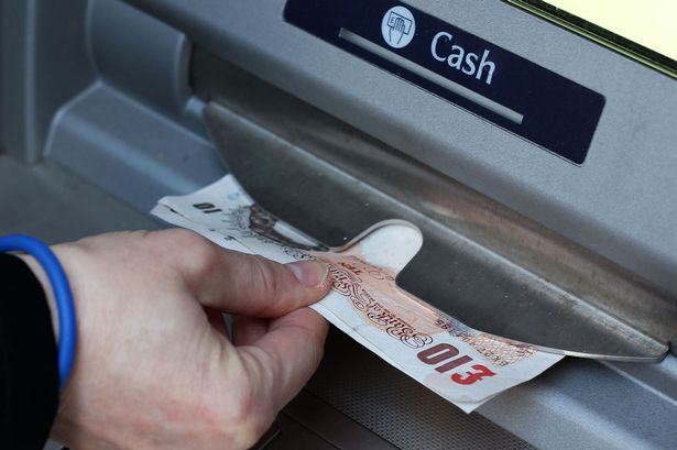 Money-being-taken-out-of-a-cash-machine